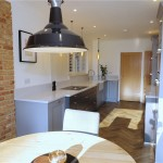 Doors from the Oxford collection in grey and copper handles with Silestone Lagoon worktops and appliances by Neff