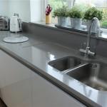 Handle less Polar white kitchen with Gris expo surfaces
